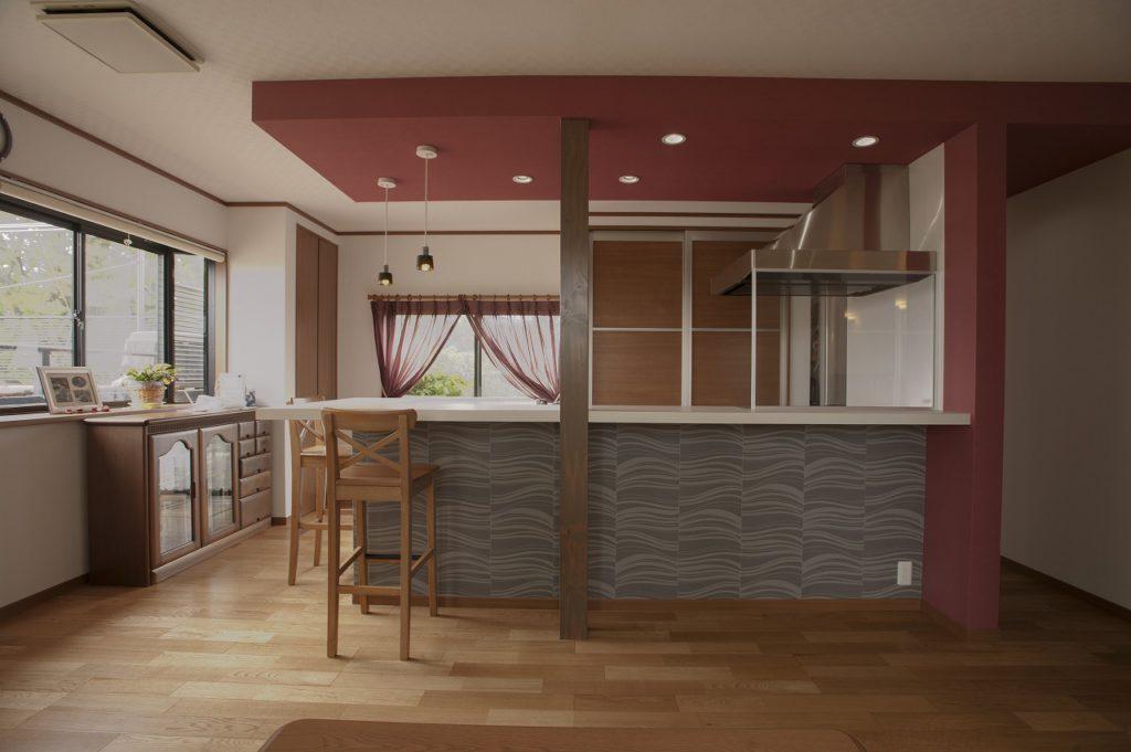 【キッチン】 キッチン上の天井を一部下げ、カーテンに合わせた 赤いアクセントクロスを貼りました。 構造上取れない柱は塗装し、アクセントにしました。
