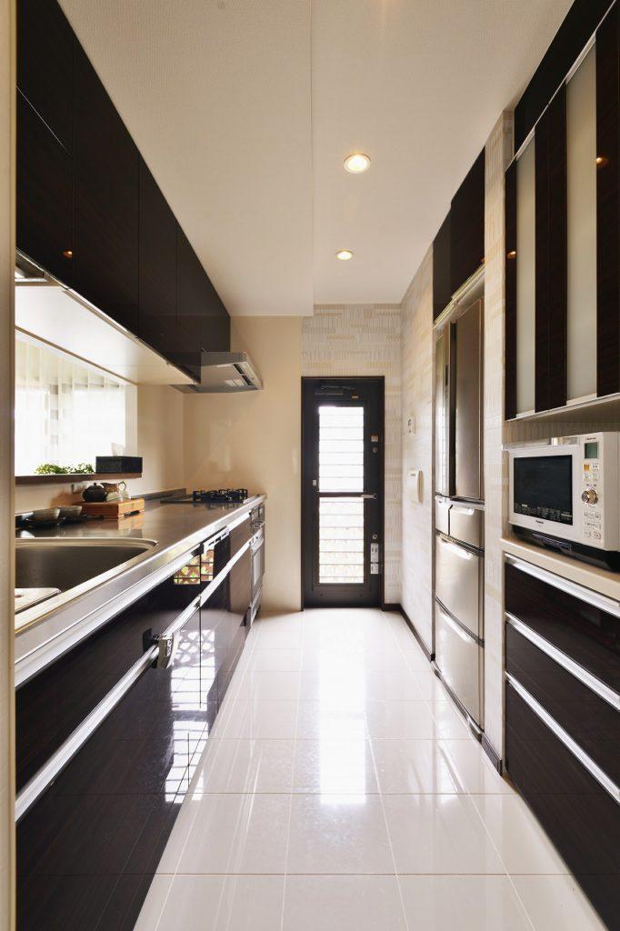 【キッチン】 ダークレオ色のキッチンと収納と鏡面ホワイトの 床のコントラストが明るいモダンテイストの キッチン空間を作り出します。