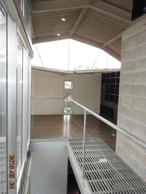 【リビング】 屋根が露出した天井は既存を活かし、 配線が見えないよう照明を設置しました。 天井には断熱塗装を施し、窓にも 遮光フィルムを張って断熱性を高めました。