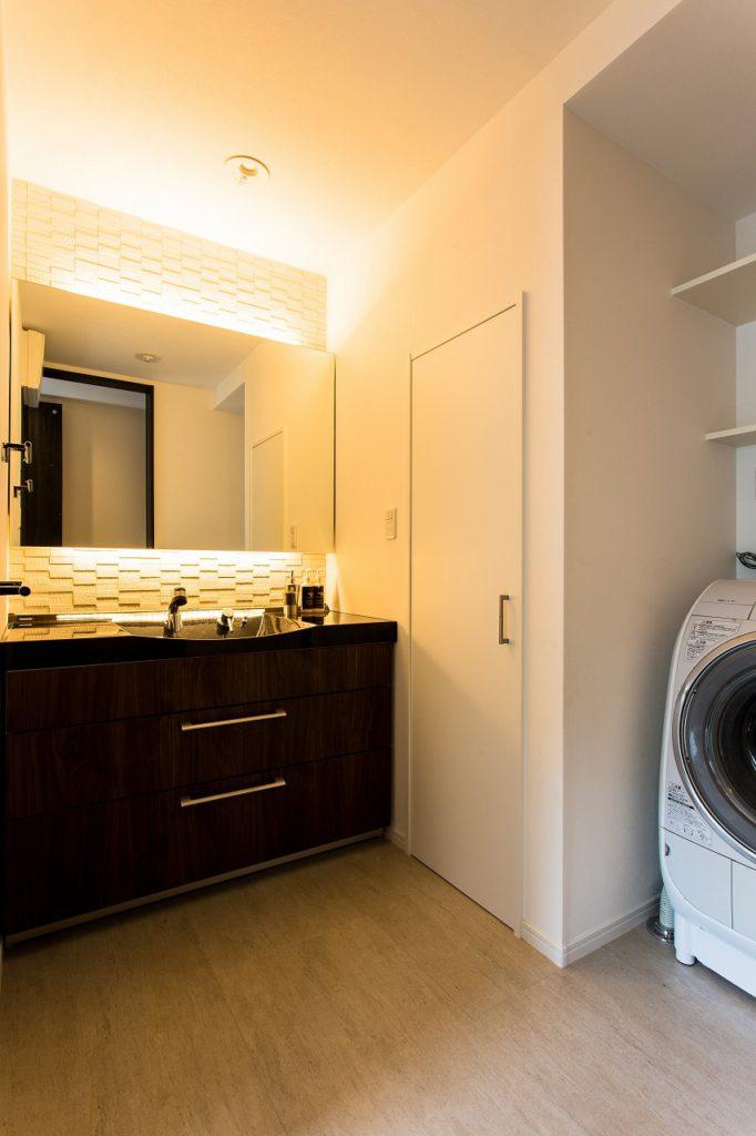 【洗面室脱衣室】 暗く狭いトイレを洗面室に。エコカラットで調湿し、階段下はリネン庫に。
