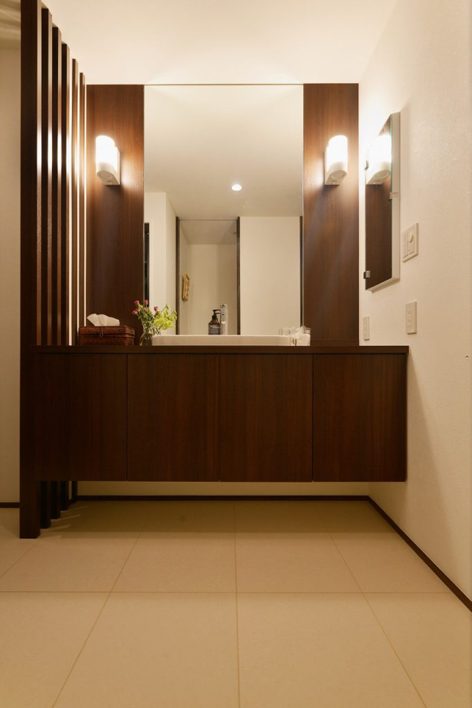 【サニタリ】 洗面と脱衣スペースを柔らかく区切る縦格子。視線は通すが空間の分離は意外としっかりできる 広さを感じるためのアイデア。