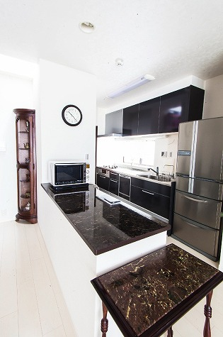 【親世帯キッチン】 大理石調のカウンターを設け、その中に 家電やゴミ箱などを設置したので、 LDKからはこまごましたものは見えず すっきりしたキッチンとなりました。