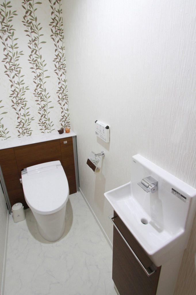 【トイレ】 タンクにほこりや汚れが付きやすいため、清掃性の良いようにタンクを隠したトイレを採用。アクセントクロスも素敵に映えました。