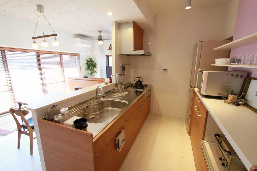 【キッチン】白い木目のオープン棚とピンクのクロスがアクセント