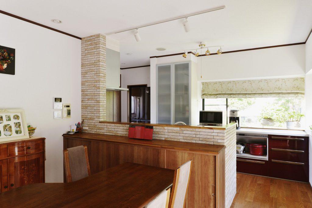【DK】 既存のダイニングテーブルや収納を活かして、キッチンの「赤」と壁面のタイルにこだわり、木目と赤が自然なデザイン