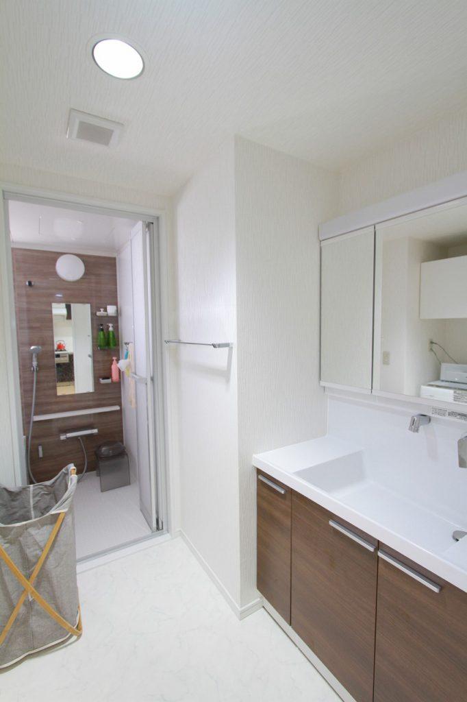 【洗面所・浴室】 洗面化粧台と、浴室のアクセントパネルを同じ茶色い木目にすることで統一感が出ました。
