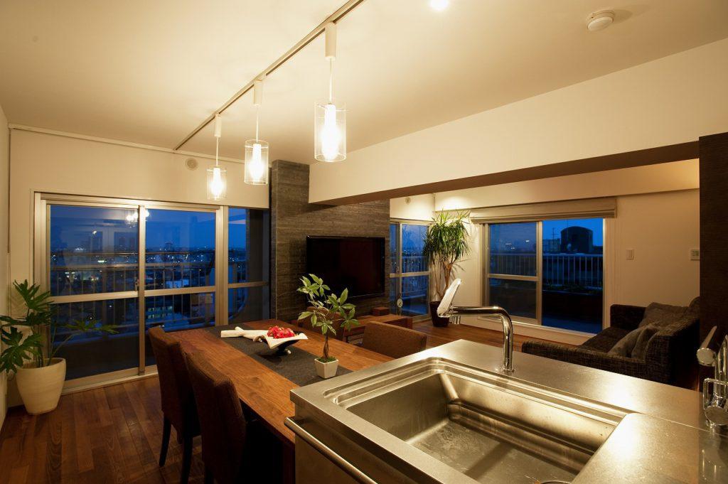 ▲最上階にある0氏邸の3面の窓がのぞめる特等席に、キッチンを配したセンターキッチンのレイアウト。 2部屋をつなぐことで露出した窓と窓の間の壁は、タイルと間接照明が印象的なテレビコーナーに姿を変えました。