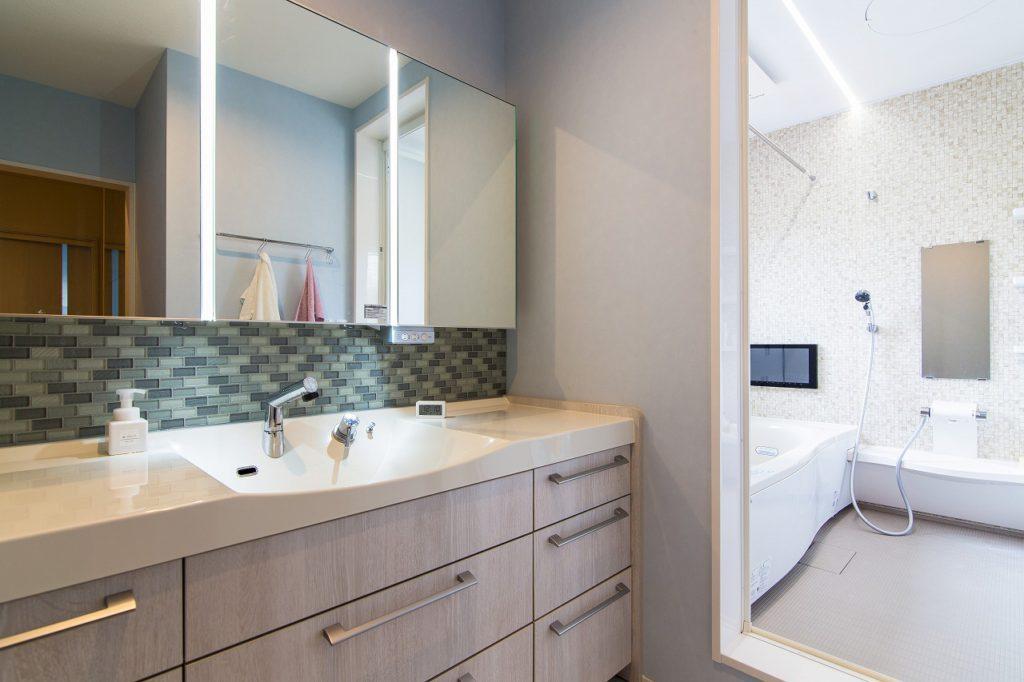 【洗面室】 大型の洗面台とアクセントタイル。UBのライン照明も印象的です。