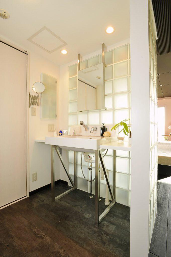▲洗面は、採光を考慮し、ガラスブロックを採用。 鏡は天井から吊るすことで、リビング側から見たときに影が目立たないよう工夫しています。洗面台も鏡も弊社のオリジナル。