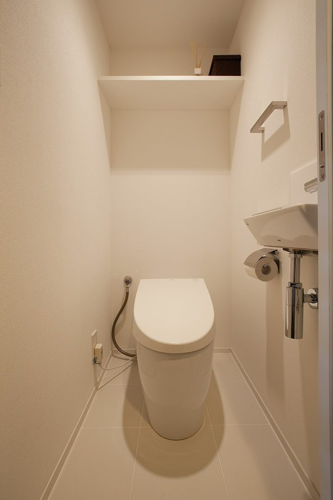 【トイレ】 洗面と同様のタイルを床に採用。便器はタンクレスにし、 新規で手洗い器を設けた。