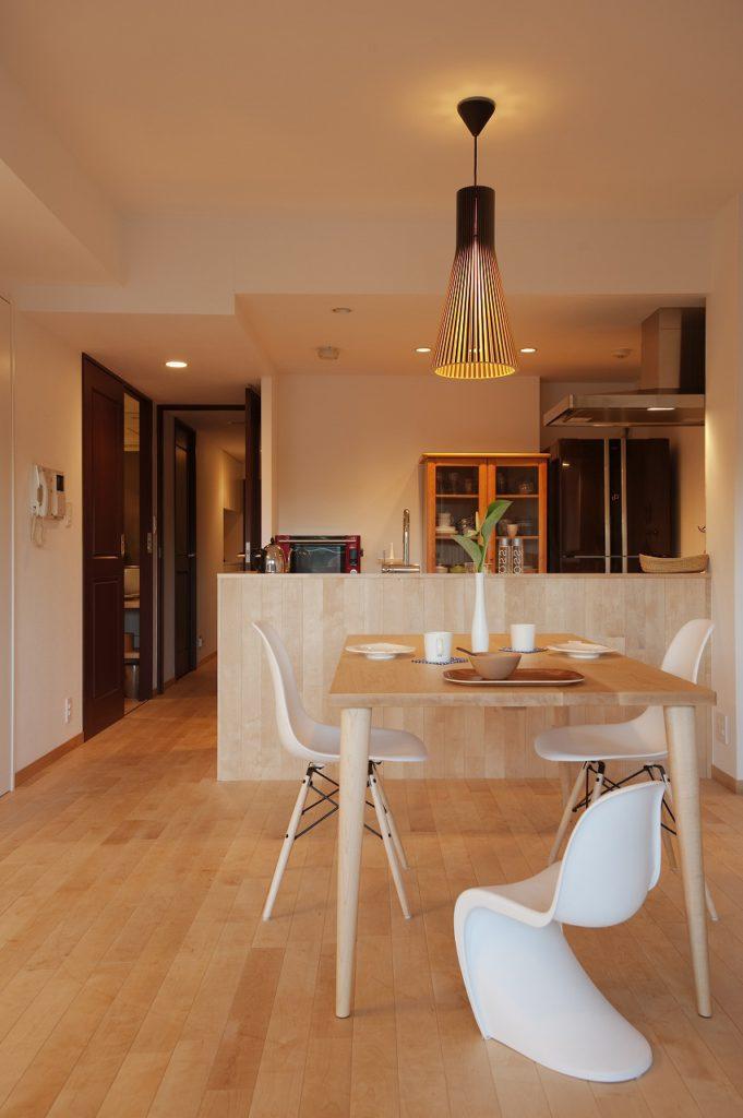【キッチン】 リビングとの繋がりを演出するために床のフローリングをそのまま腰壁として立ち上げ、キッチンの圧迫感を自然な存在としている。