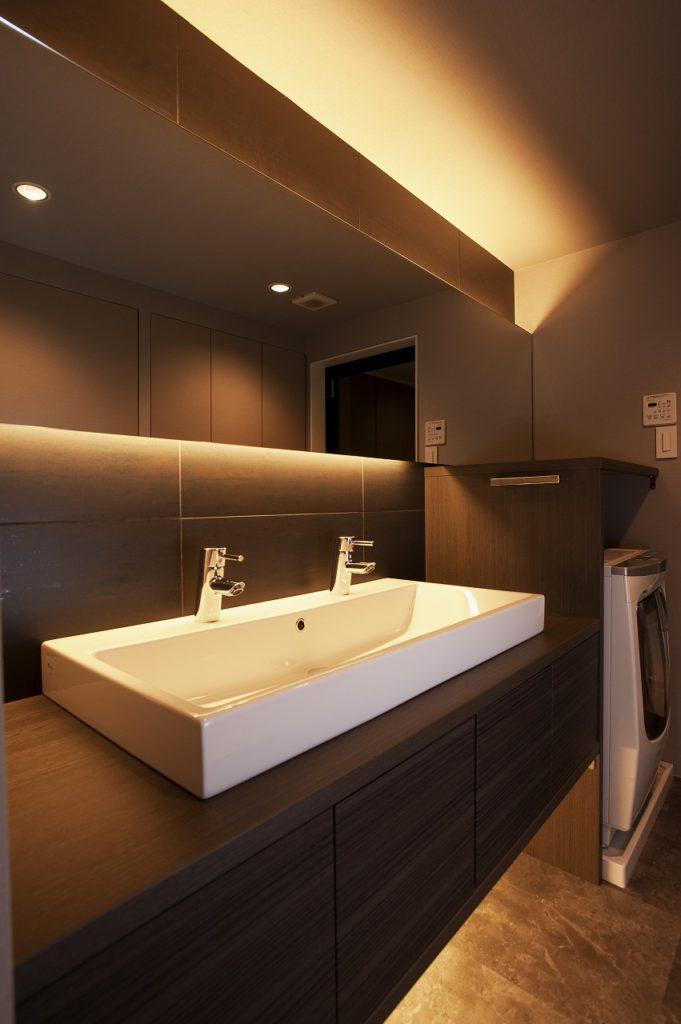 【洗面化粧台】 家族が並んで身支度ができるよう、長方形の洗面ボウルと鏡を設置。一面鏡や洗面ボウルの配置で広く見えるような視覚的効果をうまく利用しました
