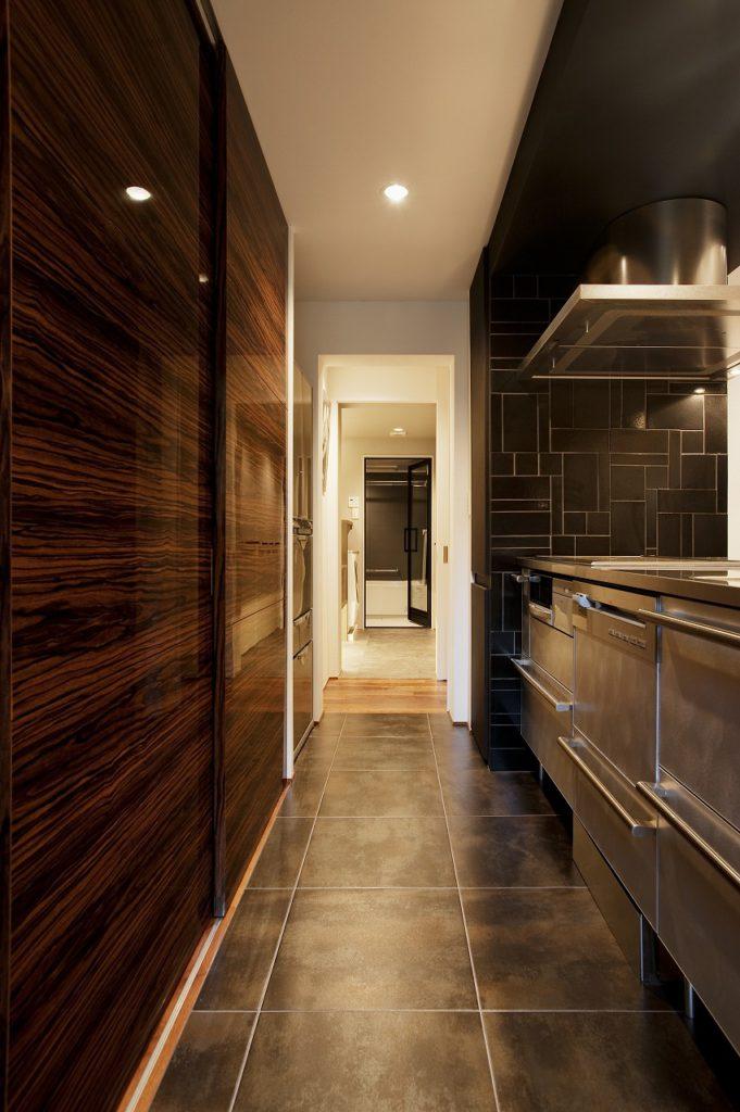 【キッチン】 キッチンの横壁の黒いタイルは形や大きさが違うものを緻密に計算して配置しました