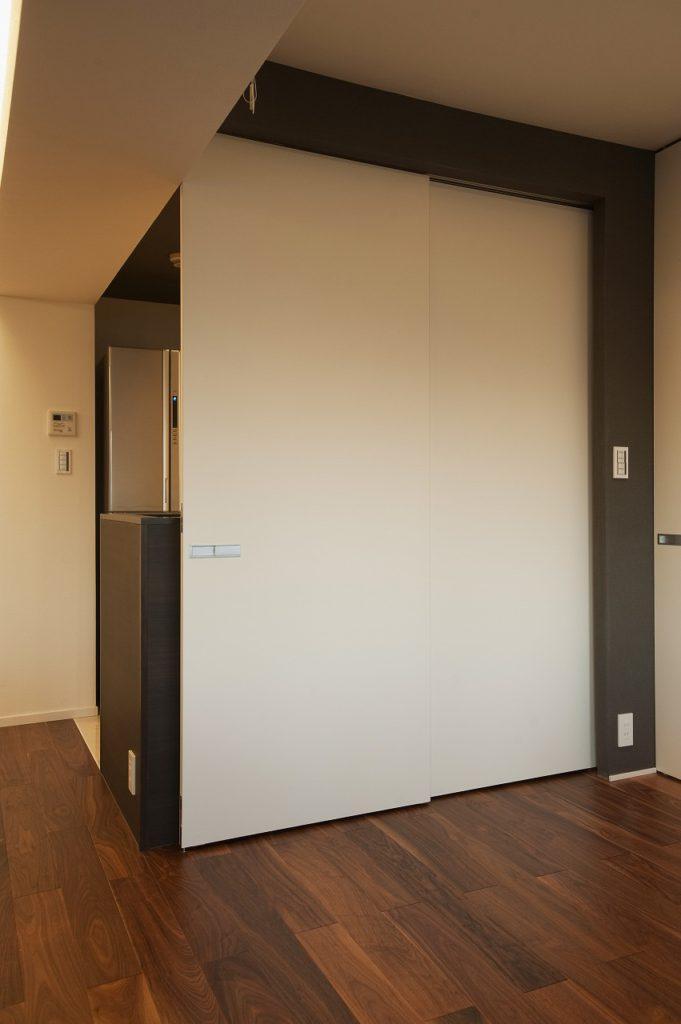 【キッチン】 キッチンはフリースペースとの区切りに2枚の吊り引戸を取り付けました。見せる見せないを自由に選べるキッチンになっています。背面収納を充実させ、オープンスタイルのキッチンを実現しました。