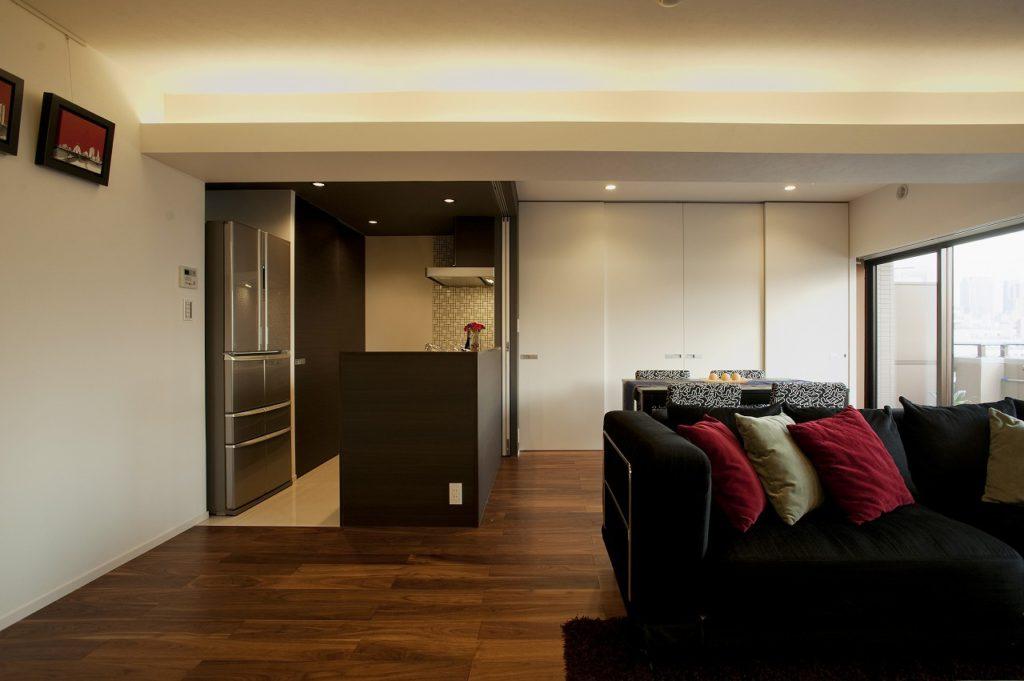 【リビングダイニングキッチン】 天井は視界に入らないように隠した光源で天井面を照らす間接照明のコーブ照明にしました。リビング床は存在感のある厚突ウォールナットのフローリング(ADVAN)を採用、キッチン床はタイルを採用しています。