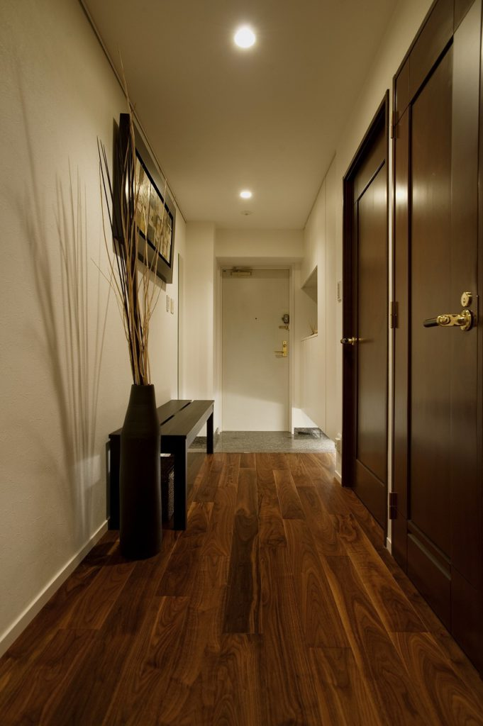 【玄関】 洋室のスペースを取り込み壁面をフラットに納めたことで、玄関をすっきり&ゆとりの空間に仕上げています。趣のあるベンチや置物が映える「住まいの顔」になりました。