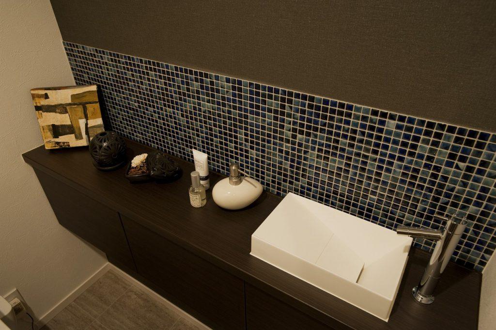 【トイレ・手洗い部分】 手洗い部分を造作、タイル、ミラー、アクセントクロスのバランスを意識しました。シャープなデザインのボウルはCERAのものを採用。紙巻器やタオル掛けはKAWAJUNのデザイン性の高いものを採用しました。
