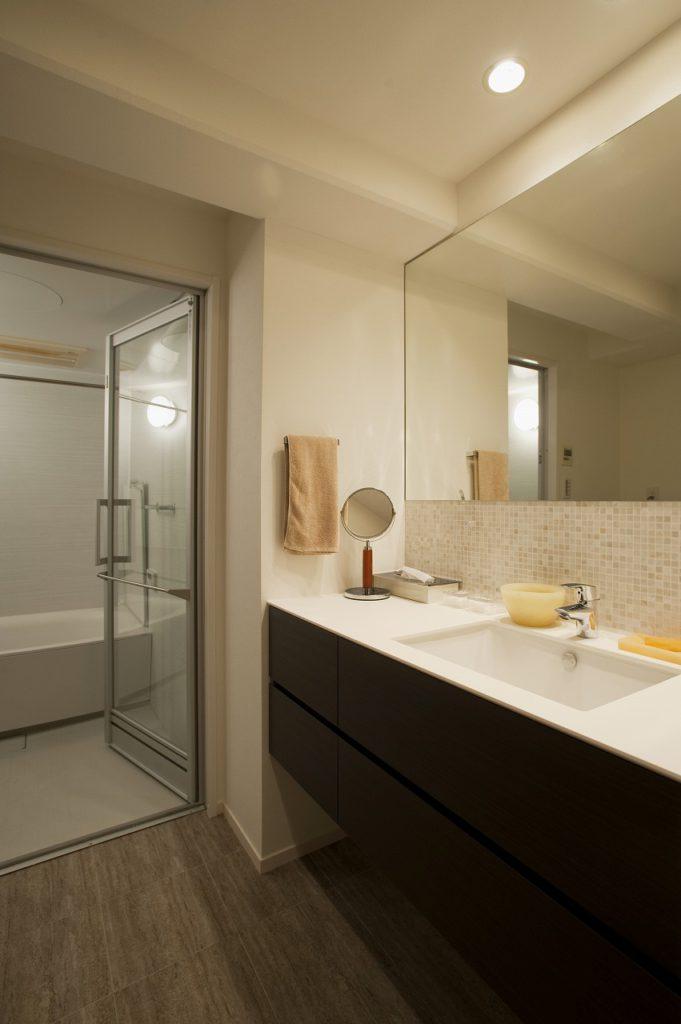 【浴室・洗面】 ホテルのような開放感のあるスッキリとした空間。浴室と洗面室との区切りのテンパーガラス戸は空間に抜けるような効果をもたらしました。サイズも1317サイズから1418へとサイズアップし、ゆとりのある空間になっています。