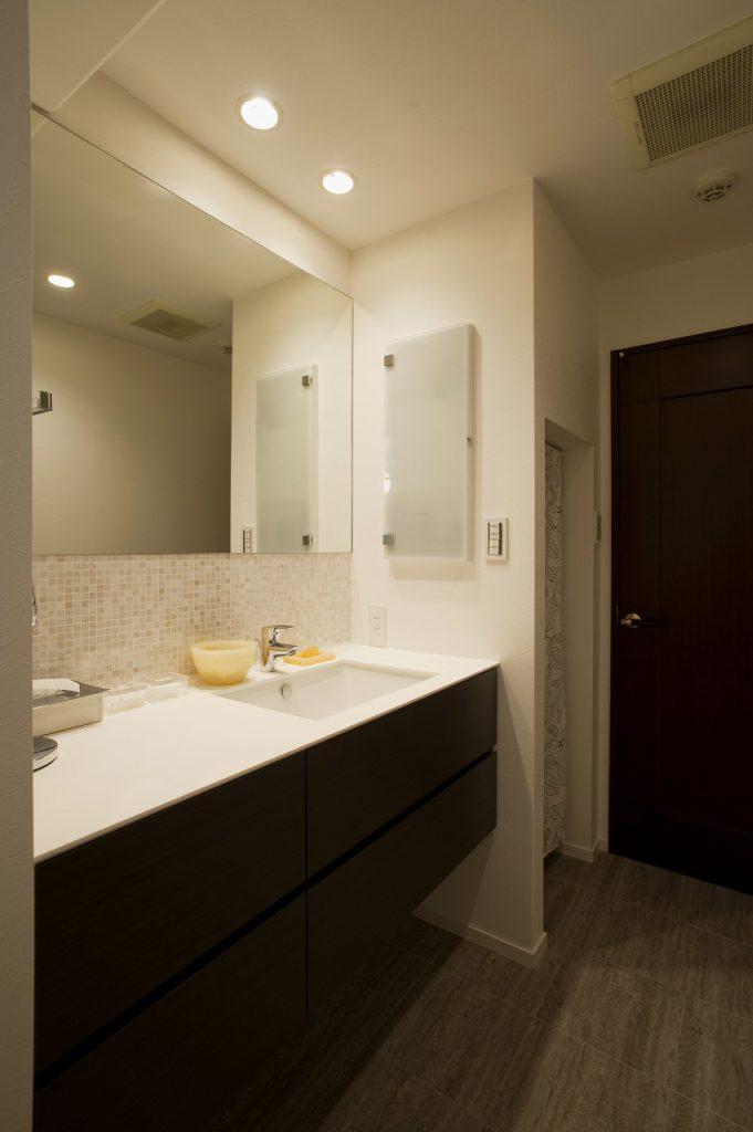 【洗面】 洗面化粧台はオーダー品です。すっきりとした一面鏡の立ち上がり部分にモザイクタイルを採用、サイズも幅120cm程度あるので存在感のある洗面化粧台になりました。メディシンボックスを化粧台脇の壁面に取り付けました。内部にはコンセントを付けるなど立ったまま使える収納はとても便利です。