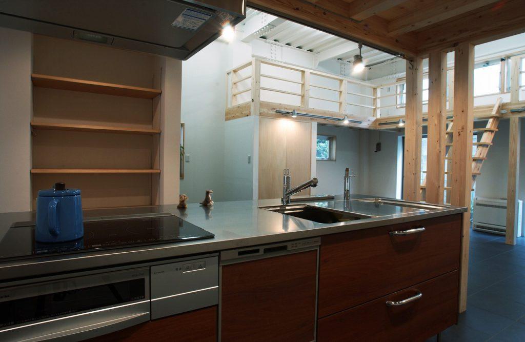 【広々ワンフロアLDK】 1FはワンフロアでLDKと寝室を兼用、床はワンちゃんのためにも瓦色のタイル敷きです。ご近所のお友達がよく訪ねて来られるので店舗とキッチンはアクセスの良い動線としました。一緒にお料理を楽しんでいらっしゃるようです。