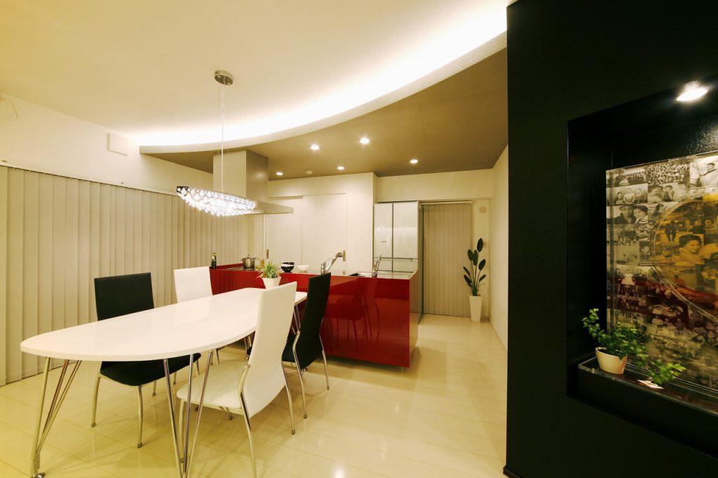 キッチンとLDとを穏やかに区切るアール状の下がり天井にはあえてグレーのクロスを貼り、室内のメリハリを強調しています(プランナー)