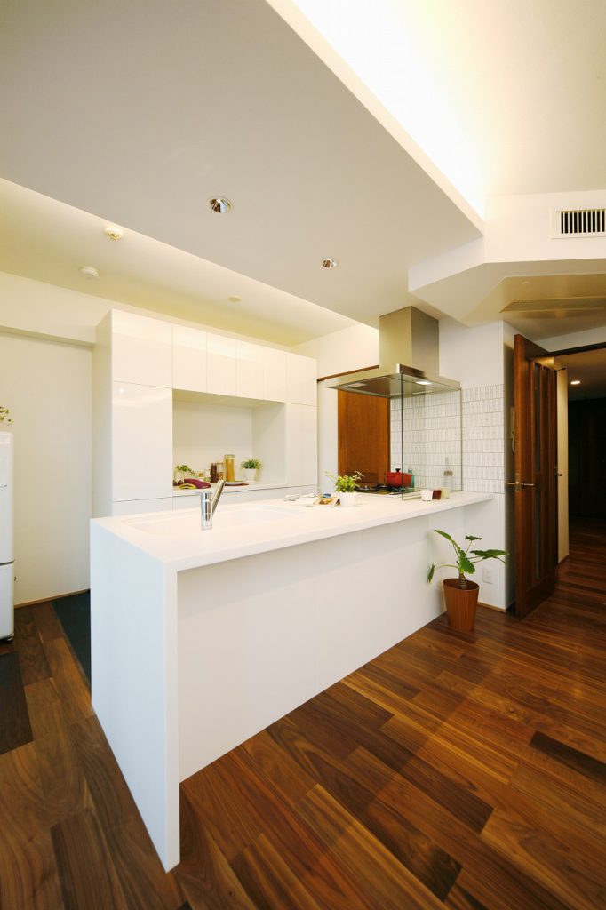 一枚天板が美しいキッチンです。揃いの食器棚を合わせ、シャープな印象を与えられるようにしました。