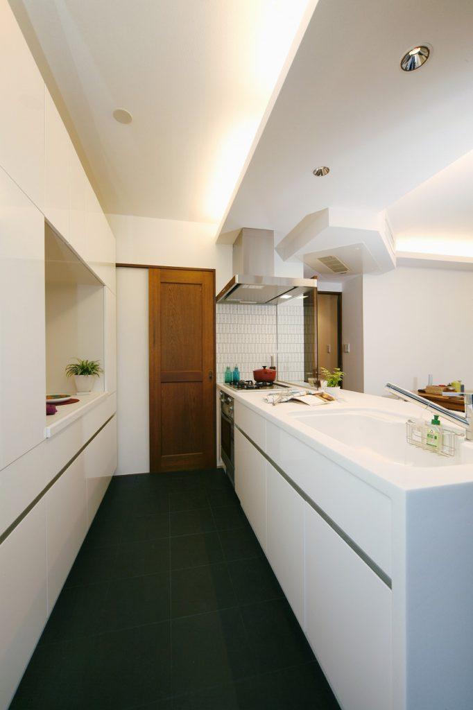 キッチンは憧れのクチーナ社のものを採用。床にはブラックのタイルを敷き詰め、空間にメリハリをつけました。ウォルナットとも好相性です。