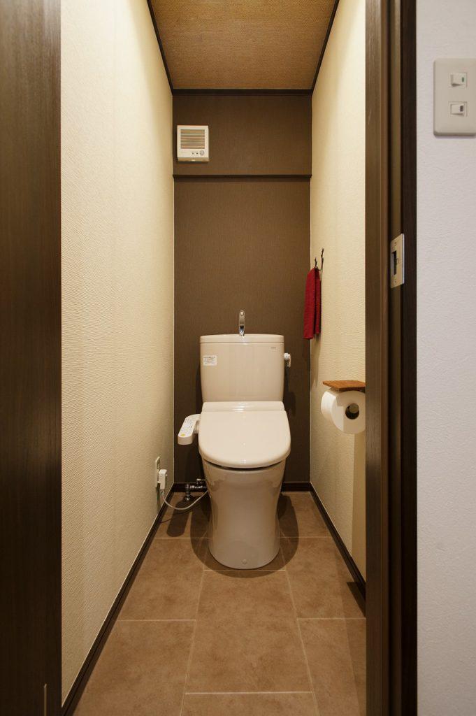 【トイレ】 タンク背面をアクセントクロスで仕上げました。