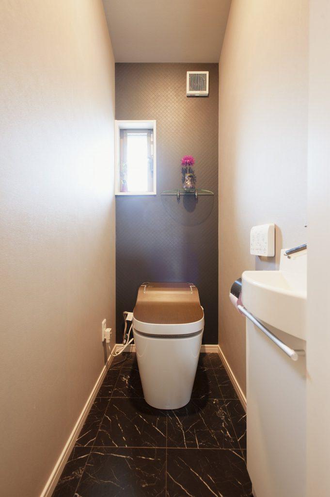 【トイレ】 背面のクロス・床・トイレの蓋の色を合わせ リビングのインテリアに合わせたコーディネートを計画。