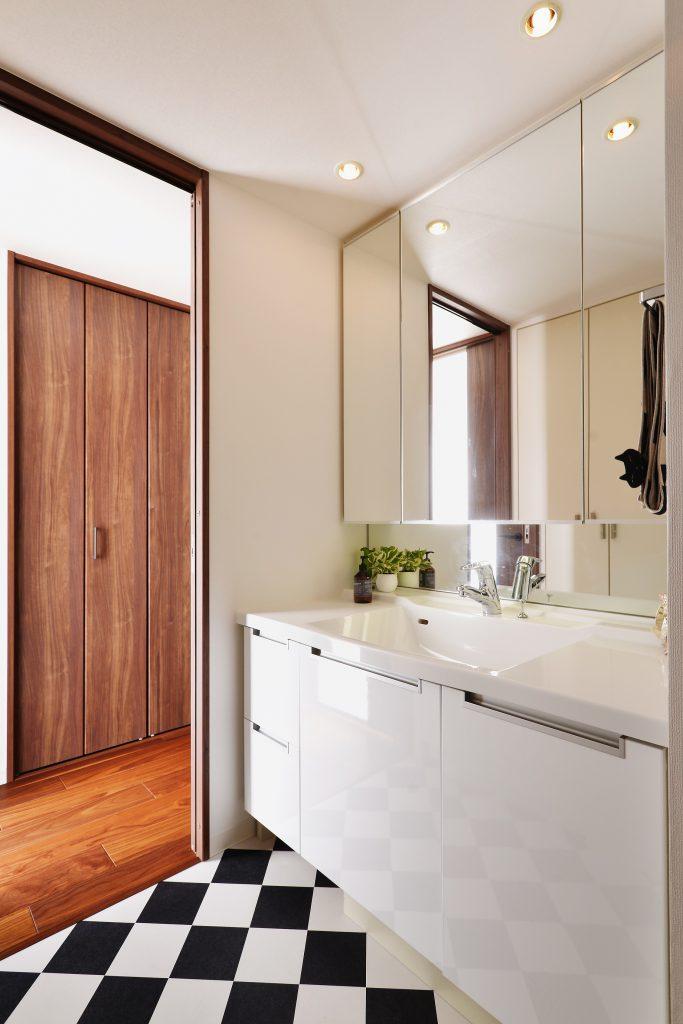 【洗面室】費用の抑えどころとして、洗面化粧台と玄関収納は既存利用しました。インテリアスタイルに馴染むように扉のみ鏡面ホワイトに変えさせて頂きました。ハーリキンチェックに張り合わせたフロアタイルが空間のワンポイントになっています。