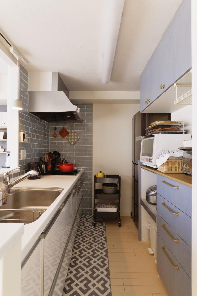 【キッチン】ブルーオークのカップボードとゴールドの取っ手が印象的。キッチン側のタイルも対になるように色を選びました。