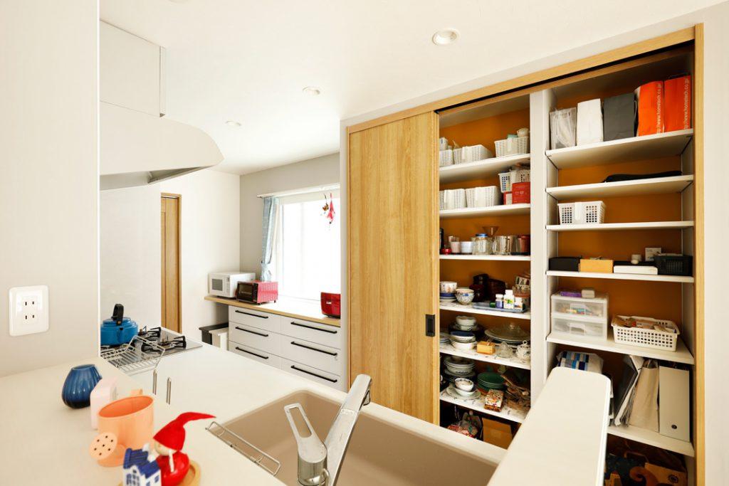 キッチンの後ろにはたっぷりのキッチン用収納と家電スペース。 造作のキッチン収納の奥は黄色の壁紙を貼り、開けるたびに楽しい気持ちになります。