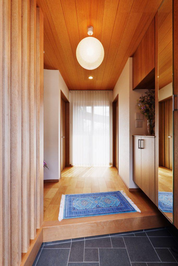 格子や天井の羽目板で明るく、落ち着いた雰囲気の玄関。正面の大きな窓からはウッドデッキにつながります。