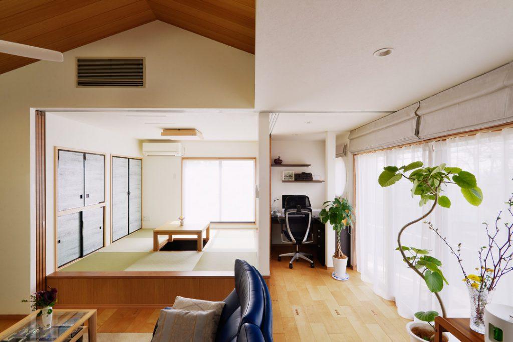 掘りごたつのあるくつろぎの小上がりスペース。その横にはご主人様の書斎スペースを。作業に集中できるL型デスクとデスク脇の丸窓から外を眺めて一息できるスペースです。