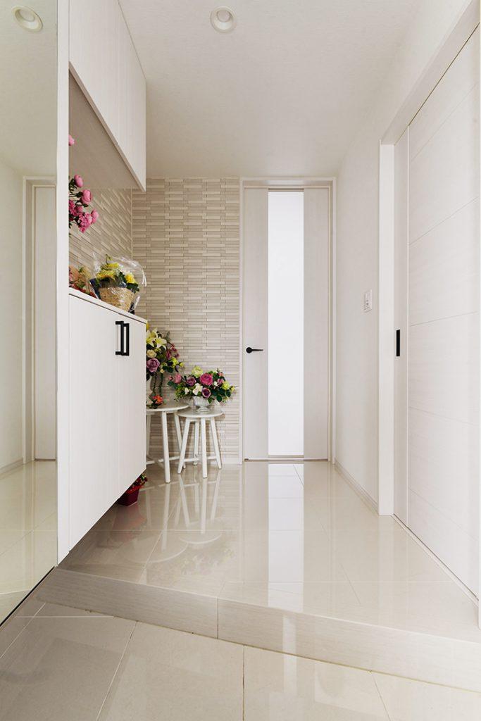 入ったときの広がりとインパクトを重視して土間からホールまでタイルを繋げて貼りました。リビングドアは天井高まで特注し、広さをアピール。