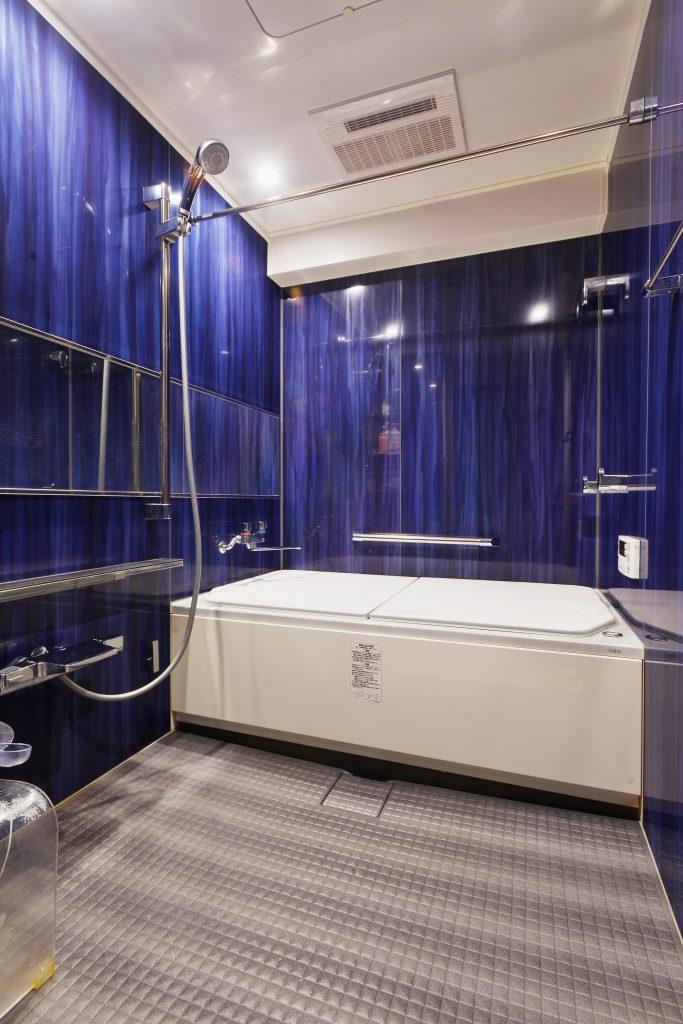 奥様セレクトのネイビーのパネルが映える広いユニットバス。介護しながらでも入りやすい広さと、大きく確保した入口の引戸でストレスフリーになりました。マンションで1418サイズのお風呂は珍しいんです