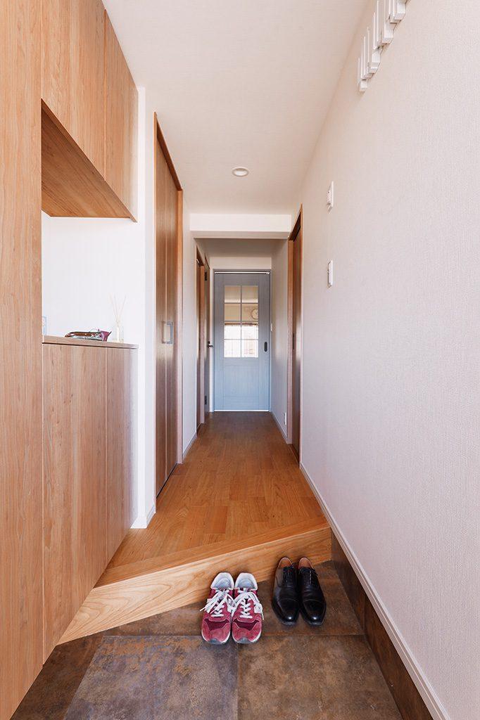 リビングへの扉のみアクセントとして違う色へ。玄関が少しでも広く見えるように框を斜めにしました