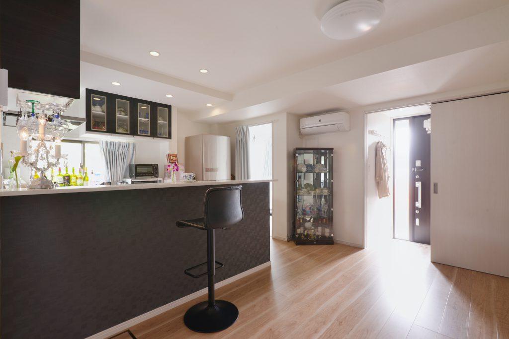キッチン上部の照明はダウンライトでスッキリ。明るい空間に奥様が大好きな黒のアクセントクロスが映えます。