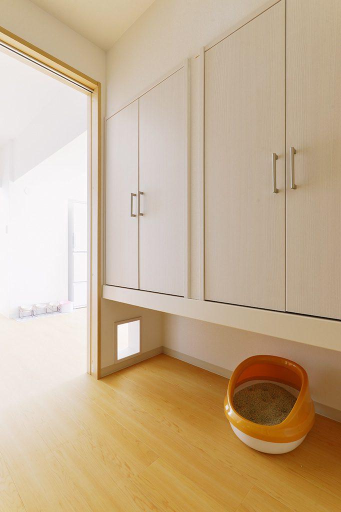 【洗面室】上部は猫グッズを全て集約できる大容量の収納、下部は猫ちゃんのトイレが3つ置けるスペース。戸が閉まっていても、専用くぐり窓から猫ちゃんが出入りできます。