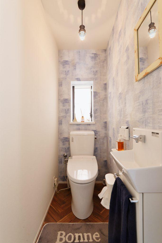 トイレ:デニム風のアクセントクロスとヘリンボーンのクッションフロアが全体の統一感とぴったりな相性です。