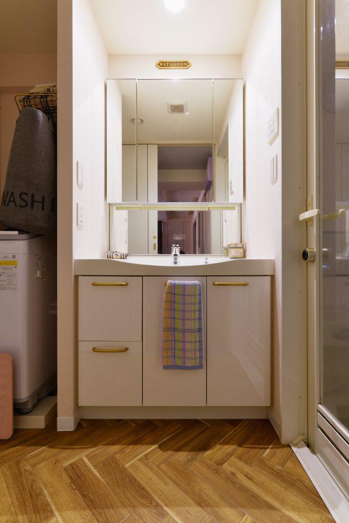 洗面室:洗面台は既存を活かし、リビングとの雰囲気を合せるために床にヘリンボーン調のクッションフロアを貼りました。