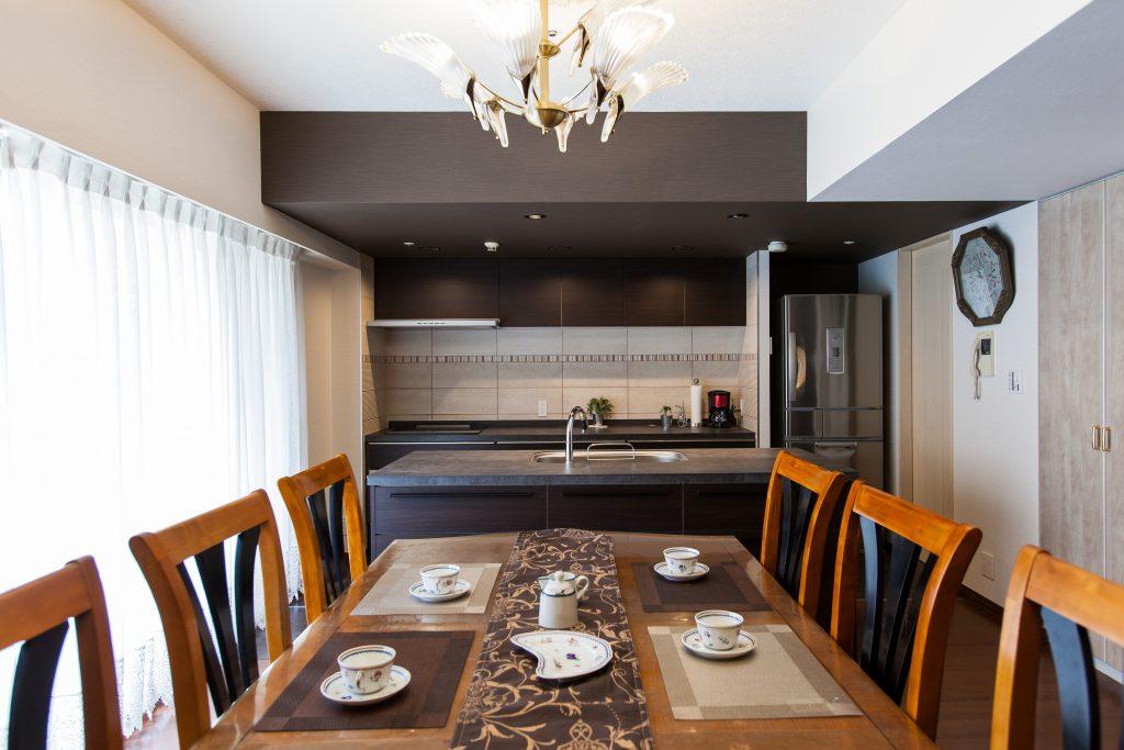 ダイニング・キッチン:天井が低いキッチンスペースはあえて重くして、ダイニング側の天井高さをアピール。キッチンの収納はもちろんダイニング側の収納も大容量