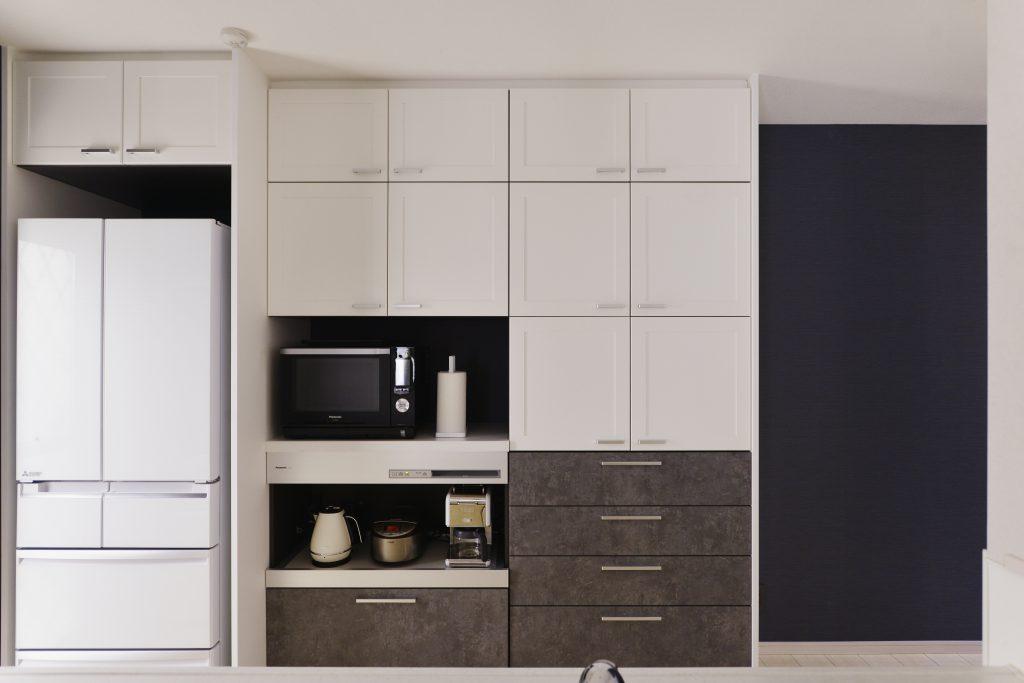 キッチン:ツートンカラーのおしゃれなカップボード。見た目だけでなく機能収納も充実しています。奥の壁にアクセントクロスを貼り奥行を広く見せました。