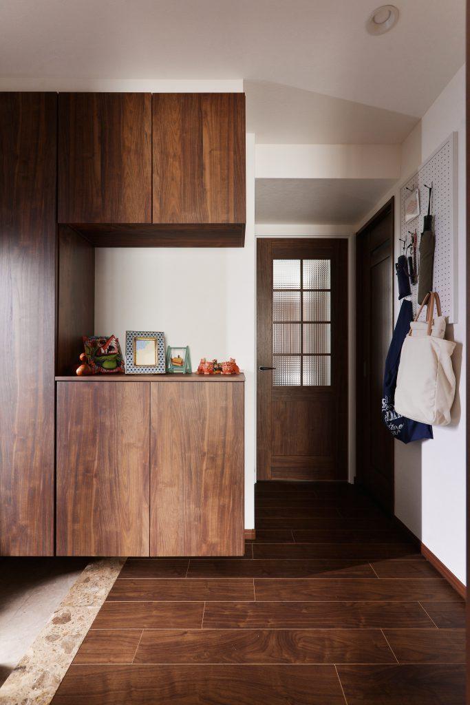 玄関:大容量の玄関収納で家族3人分の靴も楽々収納。パンチボードの壁と大理石の框がポイント