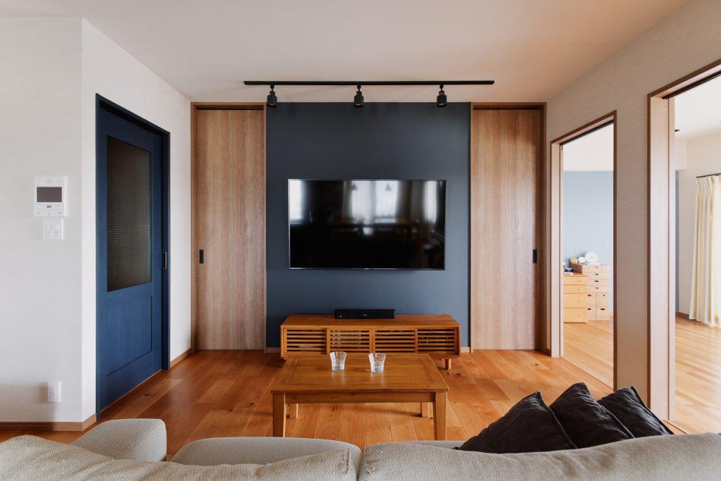 リビングダイニング:シンメトリーに印象付けたTV廻り。クローゼットへの左右の扉はあえて天井まで特注サイズで大きく作ることでかっこいい印象に。扉の向こうは大容量のファミリークロークで、不要なものはすぐに仕舞うことができます。
